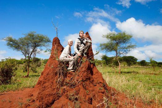 Safari vacation. Couple sitting on termite mount in Tarangire national park, Tanzania.