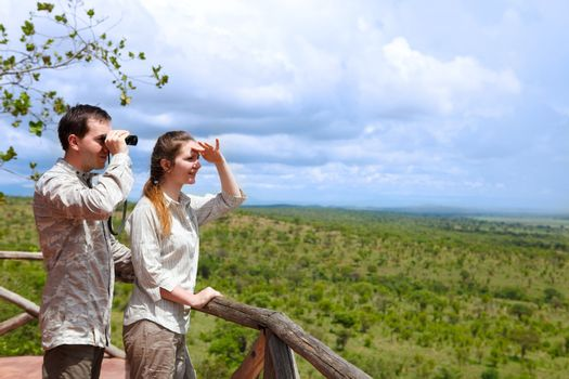 Young couple in safari clothes observing beautiful national park of Tarangire, Tanzania from balcony in lodge.