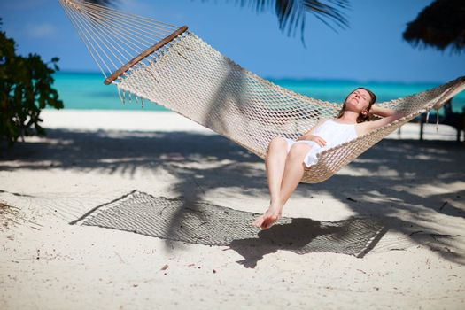Beautiful woman relaxing in hammock on tropical beach of Zanzibar island