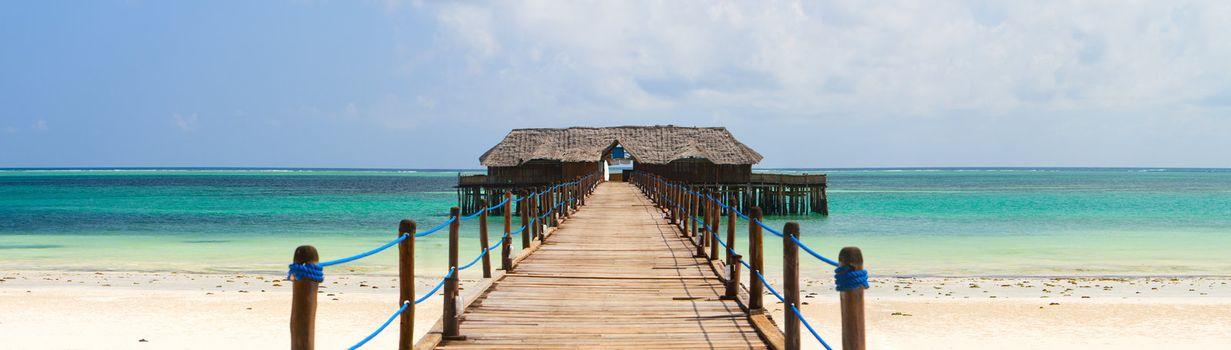 Wooden jetty on exotic beach of tropical Zanzibar island