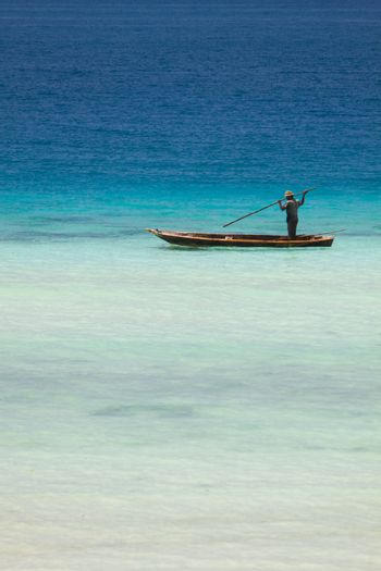 Small boat with fisherman in turquoise waters of Indian ocean close to Zanzibar coast