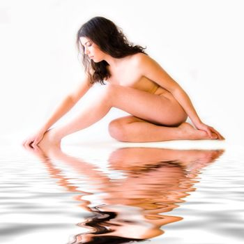Studio portrait of a naked beauty model touching her foot sitting by the pool