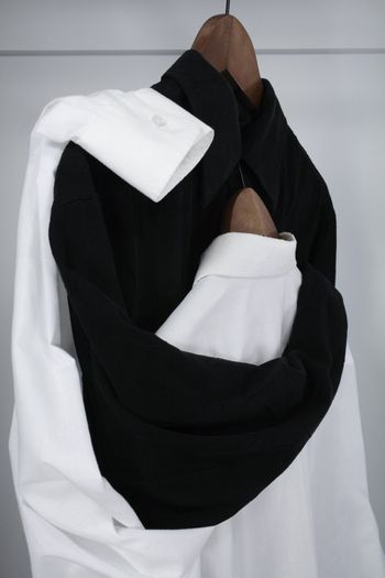 """Romance in a closet. Black shirt tenderly embracing the white shirt, which hides her """"head"""" on his chest."""