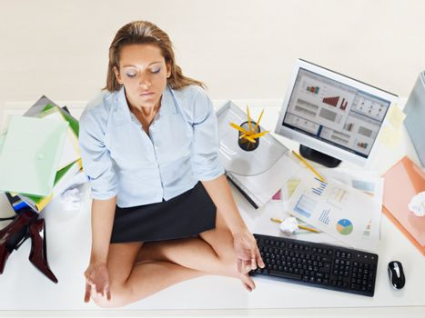 stressed businesswoman doing yoga in office. High angle view, copy space