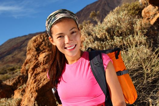 Woman hiking closeup. Young mixed chinese / caucasian female model hiking / backpacking in beautiful volcanic landscape on the volcano, Teide, Tenerife, Spain.