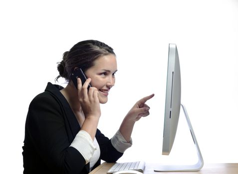 Office worker talks on her mobile whone while at her desk