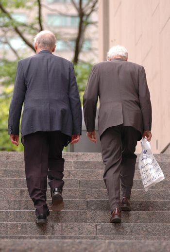 two old business man walking up the stairs