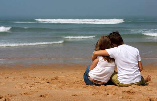 Romantic young couple in casual clothes sitting on the sandy beach and looking to ocean