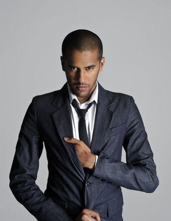 Indian fashion model stands in studio with his sharp suit