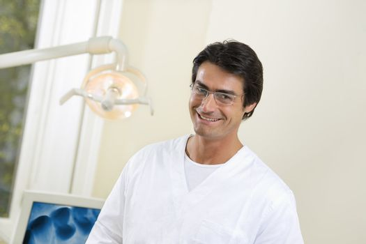 dentist smiling and standing in his office