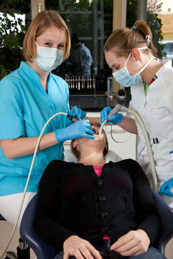 Dentist and her assistent working on a patient