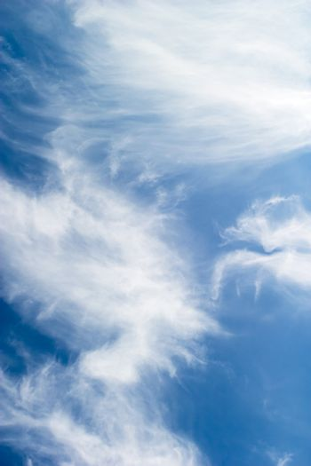 A cloud abstrct background image with whistful clouds and a deep blue sky