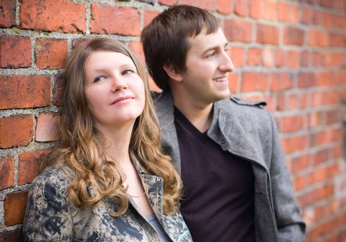 Romantic couple standing by old brick wall. Focus on girl.