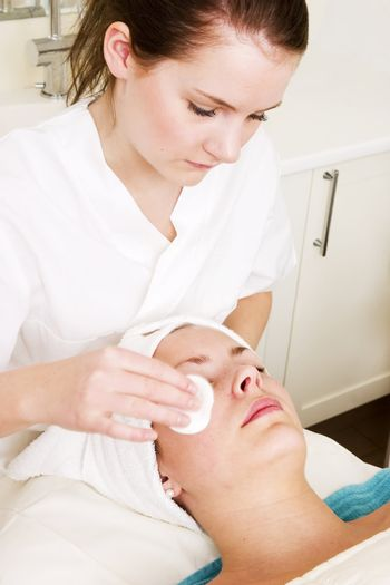 Lotion being massaged of the face at a beauty spa during a facial