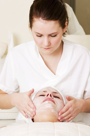 Lotion being massaged in during a facial at a beauty spa.