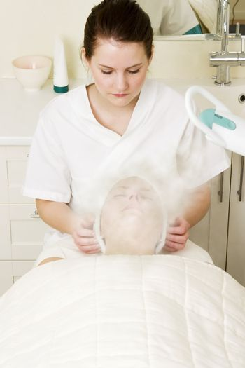 Steam treatment during a facial at a beauty spa.