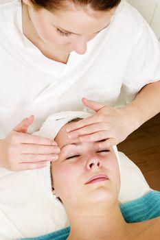 A woman receiving a facial massage at a beauty spa.