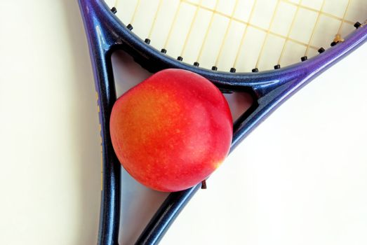 red apple in tennis racket over white isolated