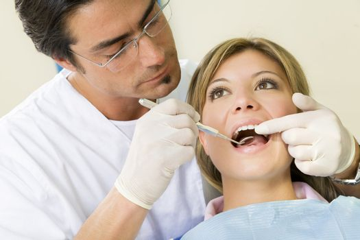young woman doing dental checkup. Dentist is using an angled mirror