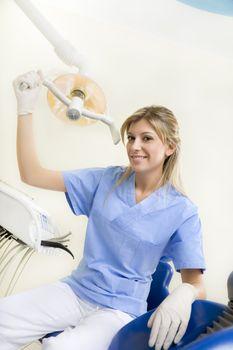 dental assistant smiling and adjusting the lamp