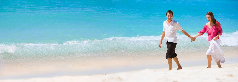 Panorama of romantic couple on white sand beach