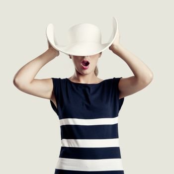 Portrait of a beautiful fashion woman posing with a hat