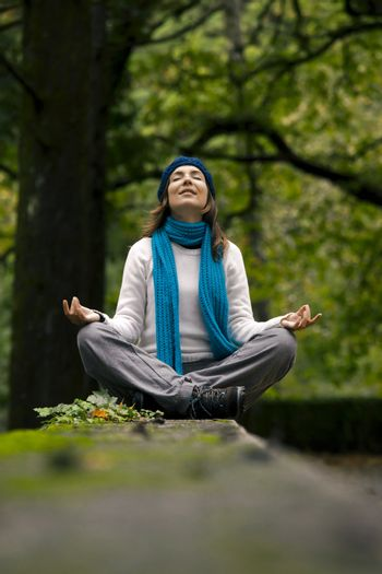 Beautiful young woman in nature making meditation exercises