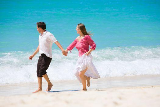 Romantic couple walking along white sand tropical beach