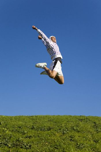 healthy lifestyle: man training outdoors and jumping high