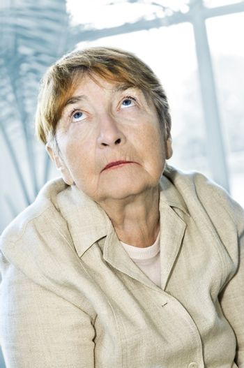 Senior woman looking up with abstract background