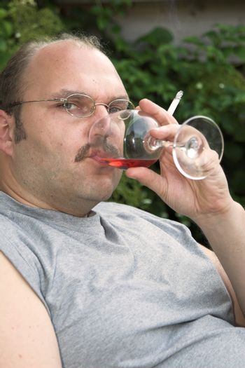 Overweight mature man sitting in a chair drinking too much and smoking too much