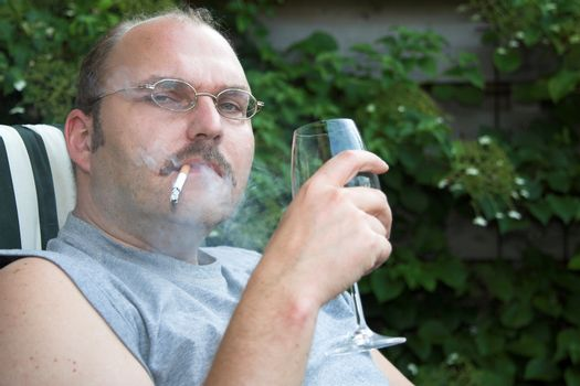 Mature man sitting in his garden chair drinking too much wine and smoking too much