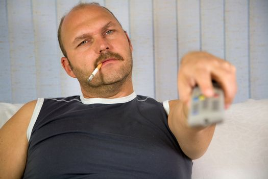 Man sitting on a couch with the remote and a cigarette in his mouth