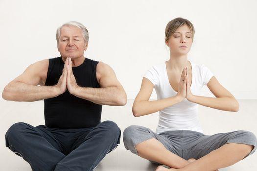 senior man and young woman doing yoga