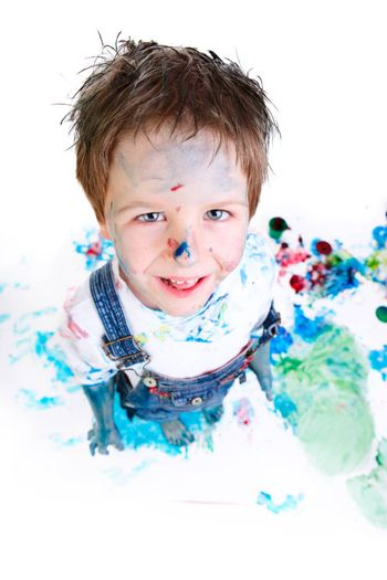 Funny photo of cute 5 years old boy painting on white background