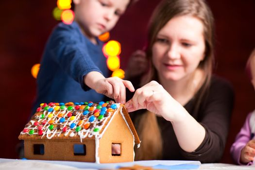 Family decorating gingerbread house on Christmas eve. Focus on house.