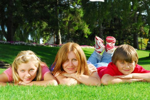 Family of happy mother and children relaxing on green grass