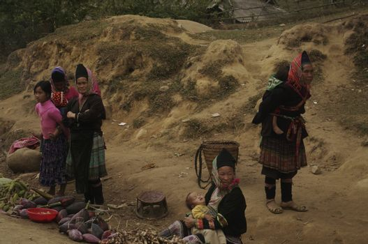 Along the road in front of the village women Phu La ethnic group sell their meager crops