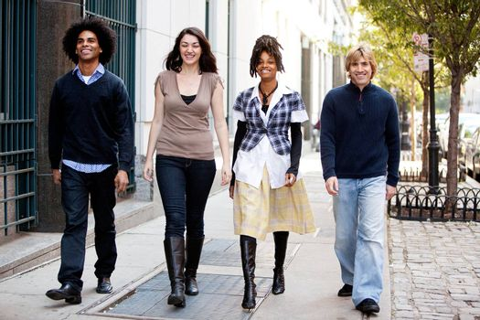 A group of friends walking on the sidewalk in an urban setting