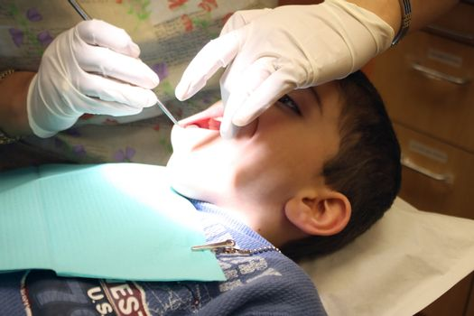 a boy gets a routine check up at the dentist