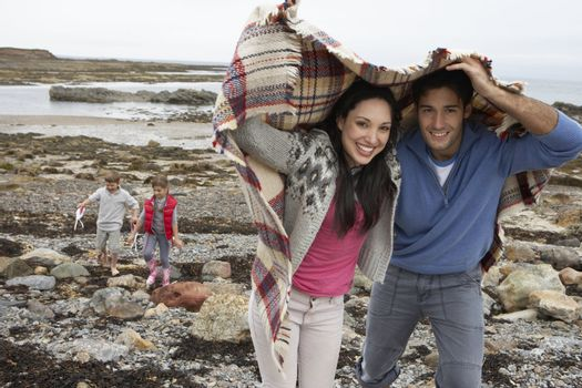 Family on beach with blankets