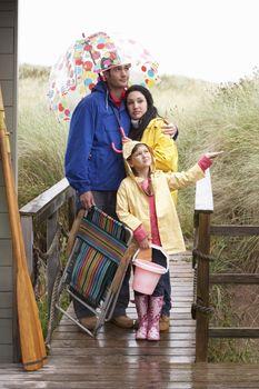 Family on beach with umbrella