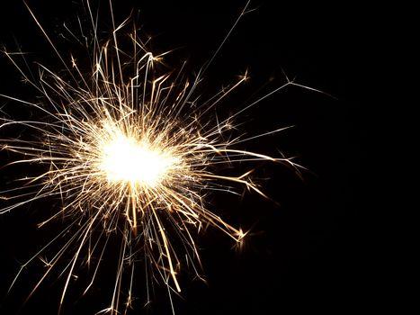 Details of a burning handheld firework over black background