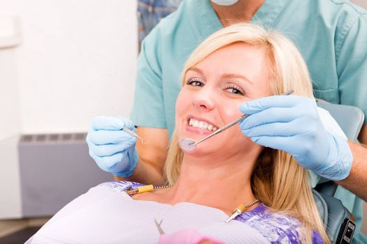 A smiling woman at the dentist ready for a check-up