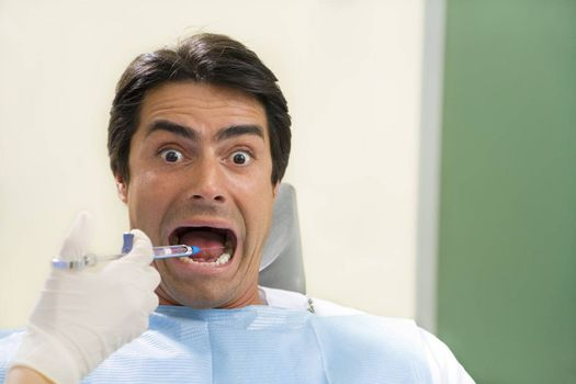 dentist holding a syringe and anesthetizing his patient. Copy space on the right