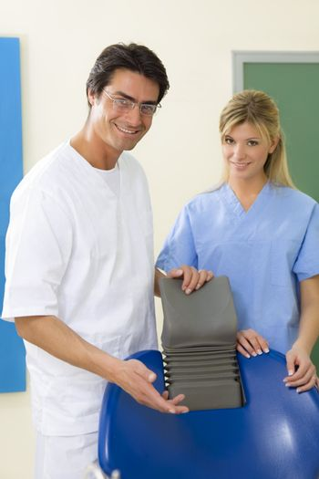 dentist and his assistant smiling and standing close to the chair