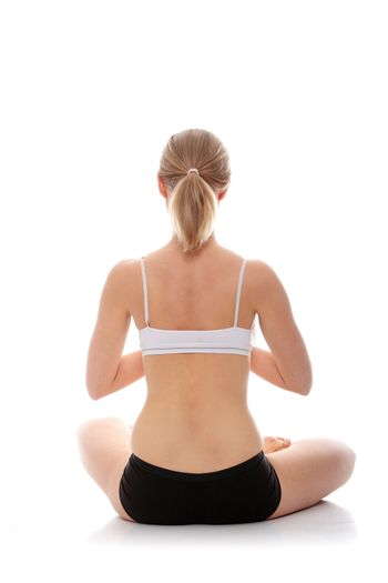 Young woman doing yoga exercise, isolated on white background