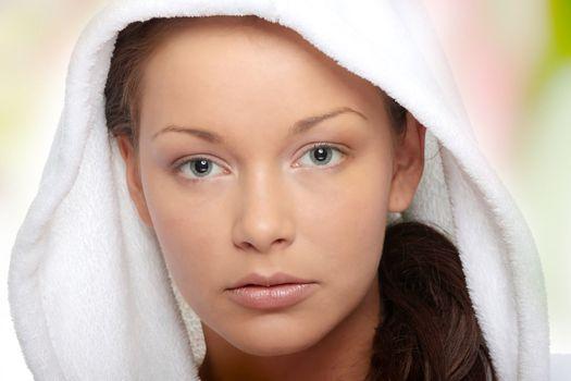 Beautiful young caucasian woman in bathrobe after bath calm portrait.