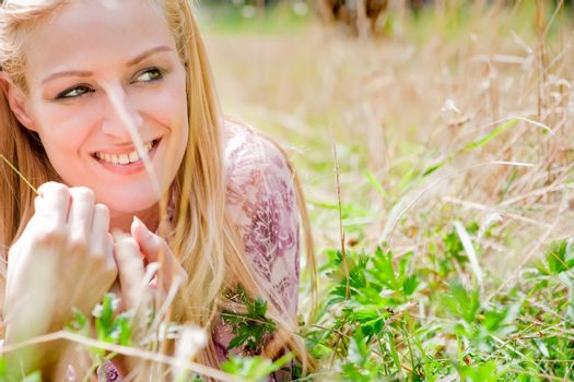 A blond woman in the park with sunny weather