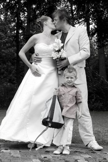 Bride and groom kissing for the photo while son watches the camera